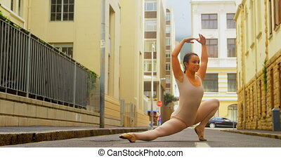 Young ballerina practicing ballet dance on the street in the city 4k