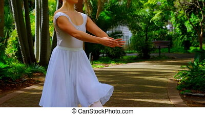 Young ballerina practicing dance in the park 4k