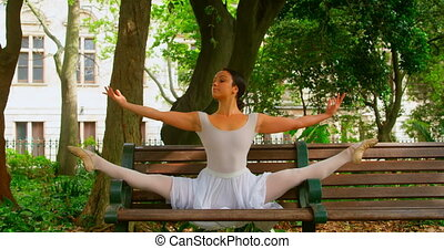 Young ballerina practicing dance on the bench in the park 4k