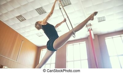 Young ballerina practicing elements with aerial hoop , slow...
