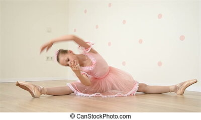 Young Ballerina Sitting On Floor In Dance Studio And Does...