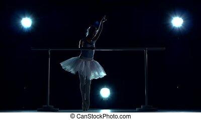 Young ballerina standing near barre