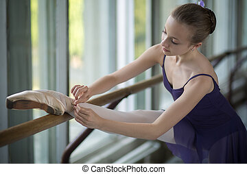 Young ballerina standing near the window, tying ribbons of point