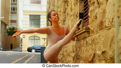 Young ballerina stretching her leg while dancing in the city...