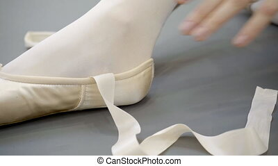 Young ballerina ties tape of pointe shoes in ballet studio.