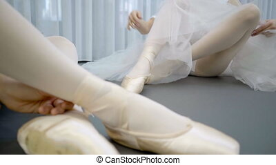 Young ballerinas are dressing pointes sitting on floor in...
