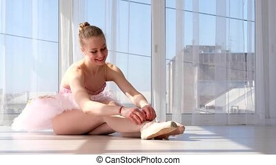 Young ballet dancer in tutu sitting on the floor and tying...