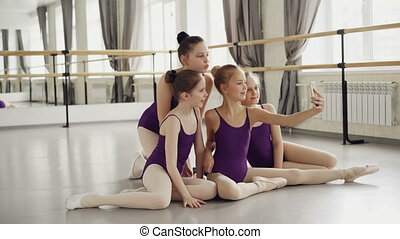 Young ballet students in bodysuits are taking selfie with...