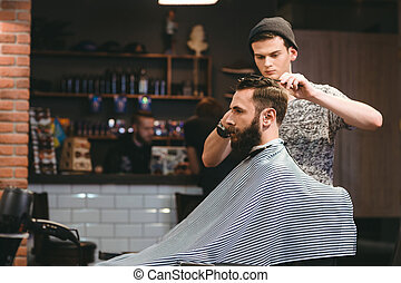 Young barber making haircut of bearded man in barbershop -...