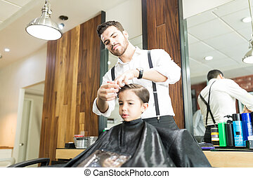 Young Barber Styling Boy's Hair After Haircut In Shop