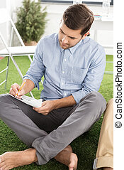 Young barefoot businessman sitting and writing on paper with pencil