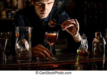 Young barman decorates glass with cocktail by burnt citrus slice.