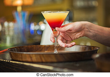 Young bartender or a waiter making a cocktail