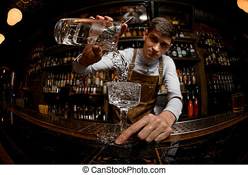 Young bartender pours drink from a jar