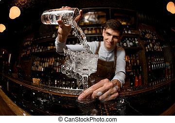 Young bartender pours drink from the jar