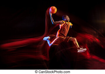 Young basketball player against dark background