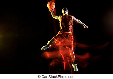 Young basketball player against dark background -...