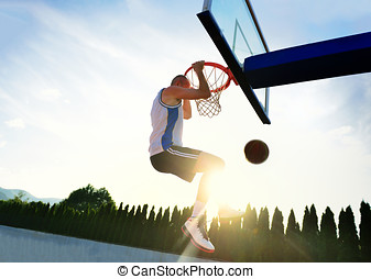 Young basketball player drives to the hoop for a high flying slam dunk