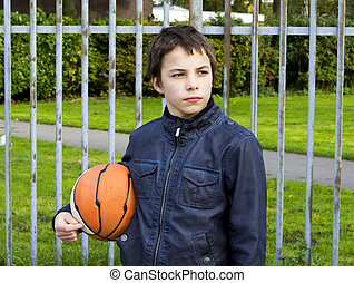 young basketball player holding ball against iron fence at the playground