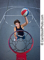 Young basketball player on the street going to the hoop.