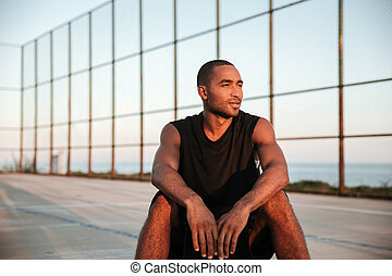 Young basketball player sitting and resting after the game