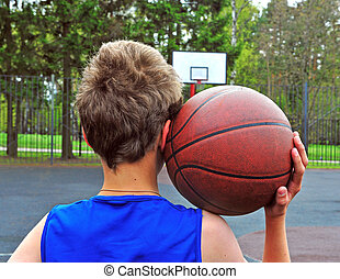 Young basketball player with a ball on his shoulder