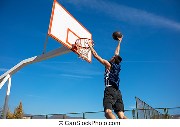 Young Basketball street player making slam dunk.