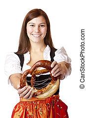 Young Bavarian woman holding Bavarian Oktoberfest Pretzel -...
