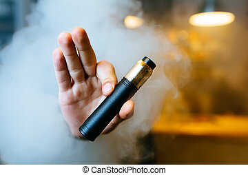 Young beard man show vaping device on his outstretched hand...