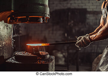young bearded blacksmith heats the metal