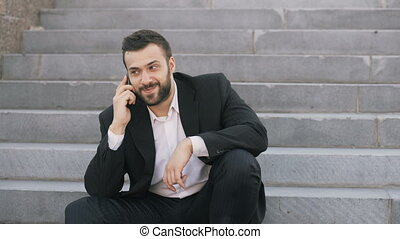 Young bearded business man talking on cell phone making...