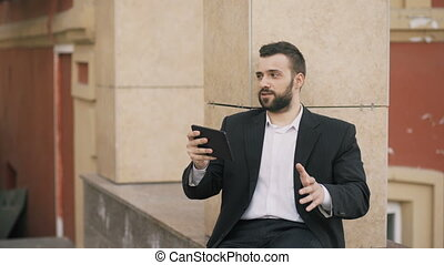 Young bearded business man talking on tablet computer having video chat business meeting. Businessman using app to have video conference conversation