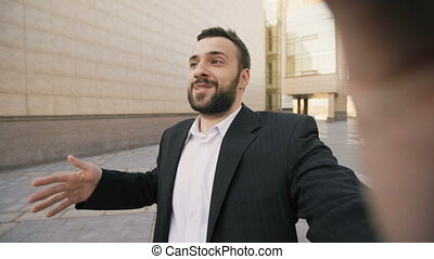 Young bearded business man talking smartphone having video chat business meeting. Businessman using app to have video conference conversation