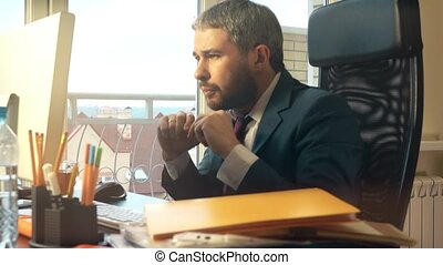 Young bearded businessman getting angry and breaking the...