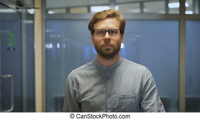 Young bearded businessman rearranges glasses