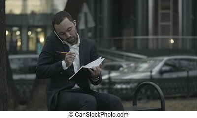 Young bearded businessman talking by phone and writing in diary, working with notes at green park.
