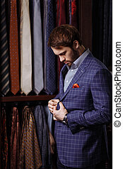 Young bearded businessman trying on custom tailored suit,...