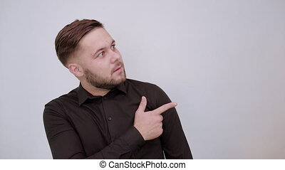Young Bearded Dark Haired Man In Black Stylish Shirt On White Background, Confused Male Shows Direction Forefinger. The Concept Of Guilt, Slander. Human Relations