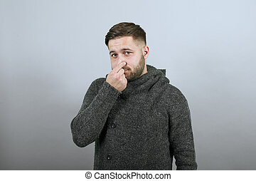 Disappointed Male Unpleasant, Covered Nose With His Hand From Bad Smell