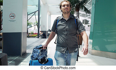 Young bearded happy man with backpack pulling suitcase in modern airport terminal. Travelling handsome guy walking away with his luggage