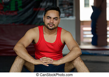 Young bearded Indian man at the gym