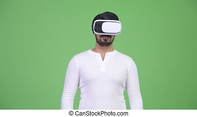Young bearded Indian man using virtual reality headset -...