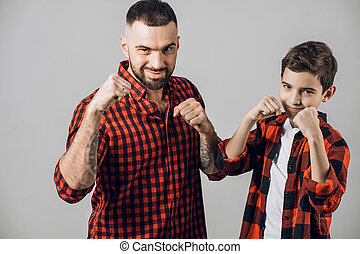 young bearded man and his son are practising boxing. close up photo. isolated gray background. studio shot. parenthood. child care, family tradition