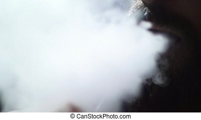 young bearded man in glasses smokes a hookah and blow out smoke closeup on black background in slow motion in 4k