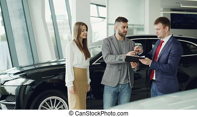Young bearded man is buying car for his attractive wife signing documents shaking hands with manager and getting key fob then giving it to woman, she is kissing and hugging him.