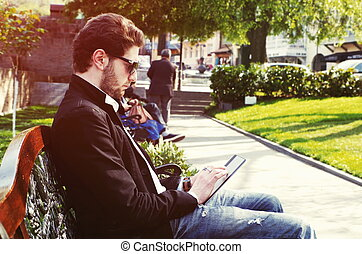 young bearded man outdoors with tablet