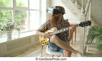 Young bearded man sitting on chair learning to play guitar...
