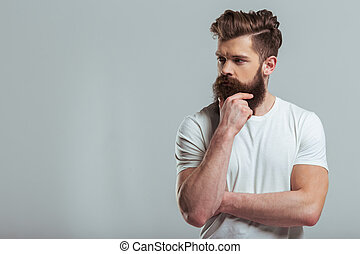 Young bearded man - Handsome young bearded man is keeping...