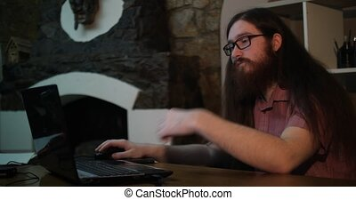 Young bearded man wearing glasses working with laptop in dark office late at night, his face lit up by screen