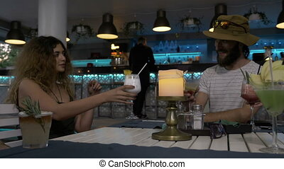 Young bearded man with his girlfriend drinking tasty...